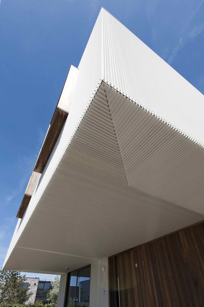 The ribbed aluminum covers the facade and the underside of the extended upper floor.