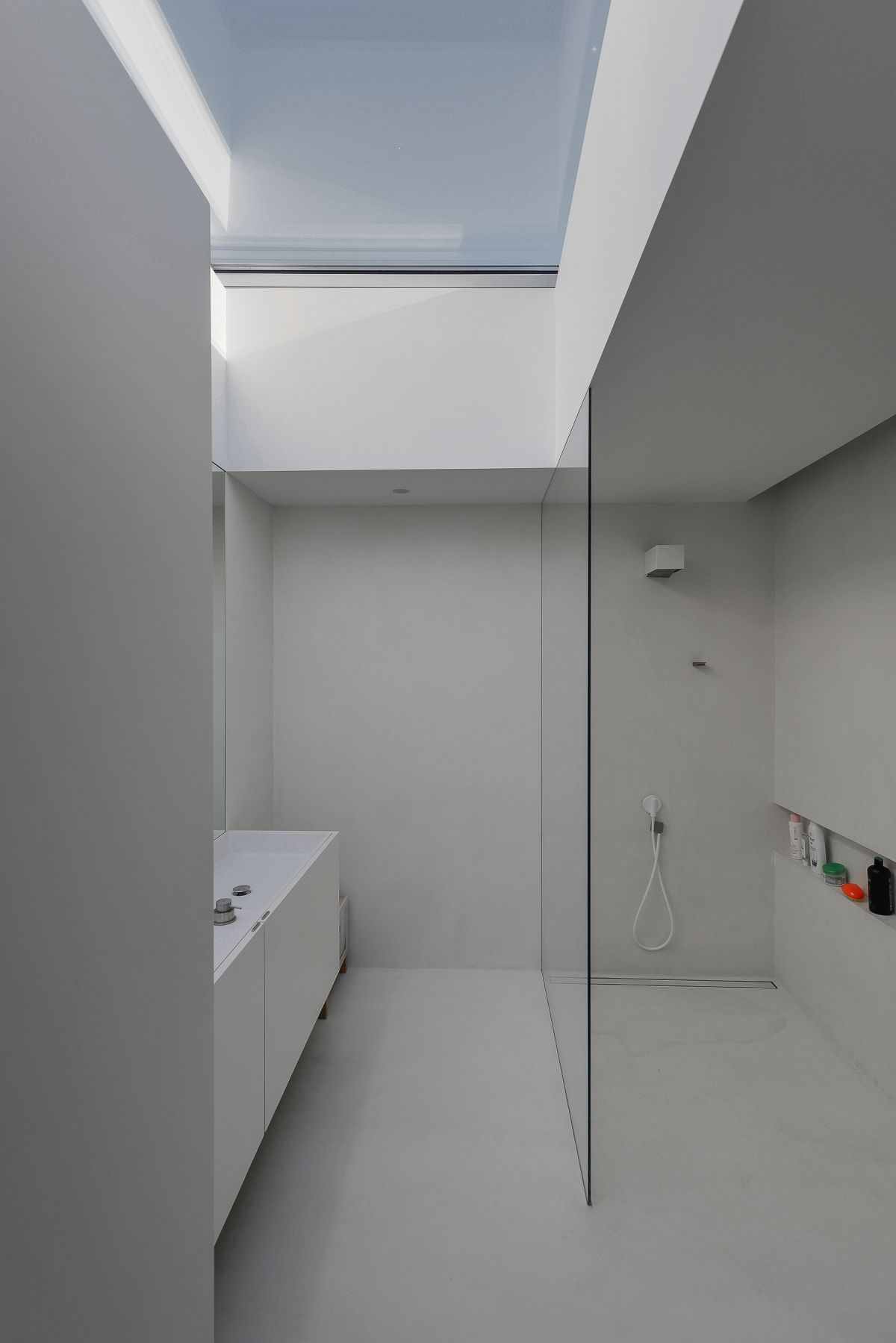 An all-white room and plenty of glass make for a modern bathroom.