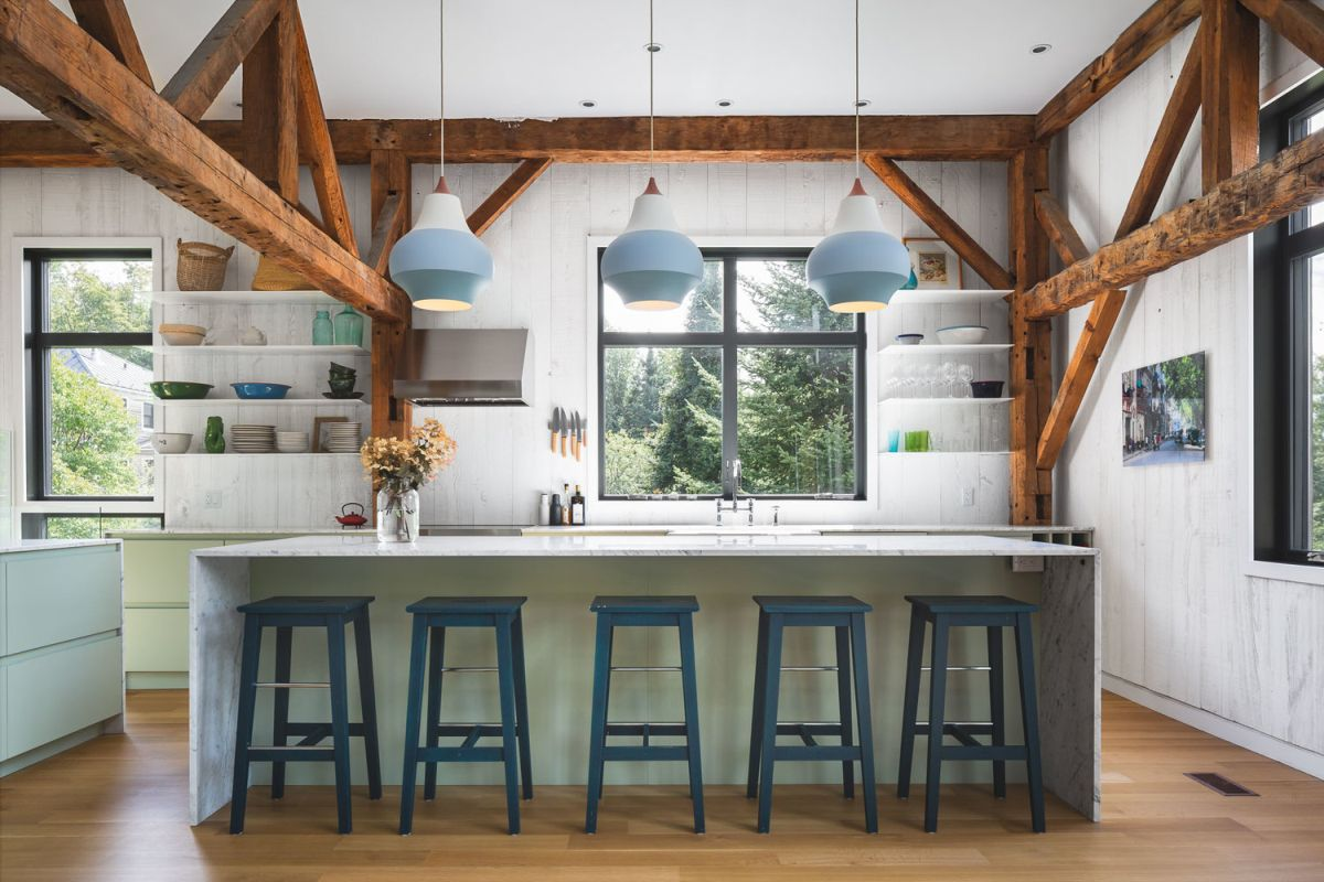 The kitchen is part of the open floor plan and features exposed wooden beams and a view of the garden