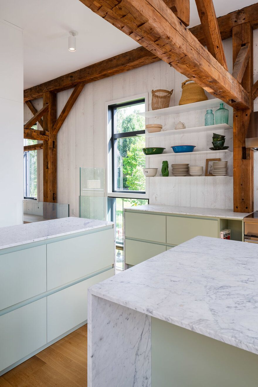 The white marble counters add an elegant and timeless vibe to the kitchen and go well with the wooden elements