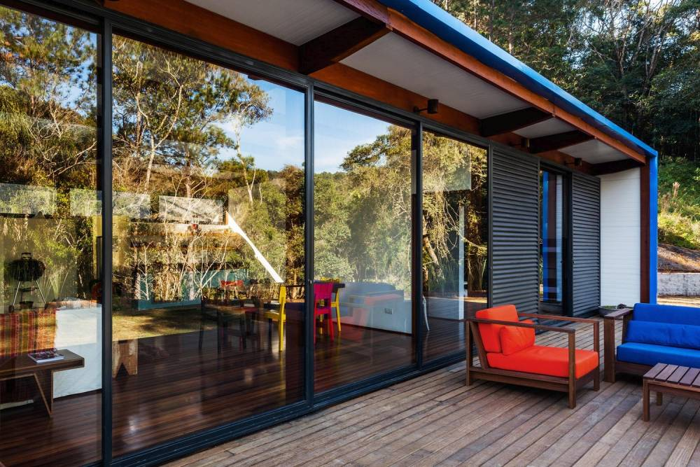 The glazed walls and sliding glass doors allow the living area to be exposed to a view of the beautiful green surroundings