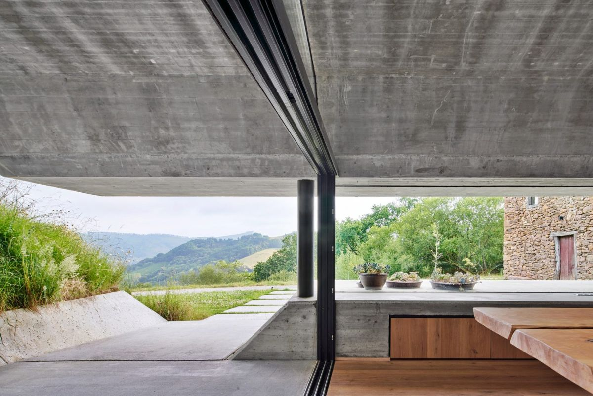 The roof forms an overhang as it extends over the terrace, framing the mountain in the distance
