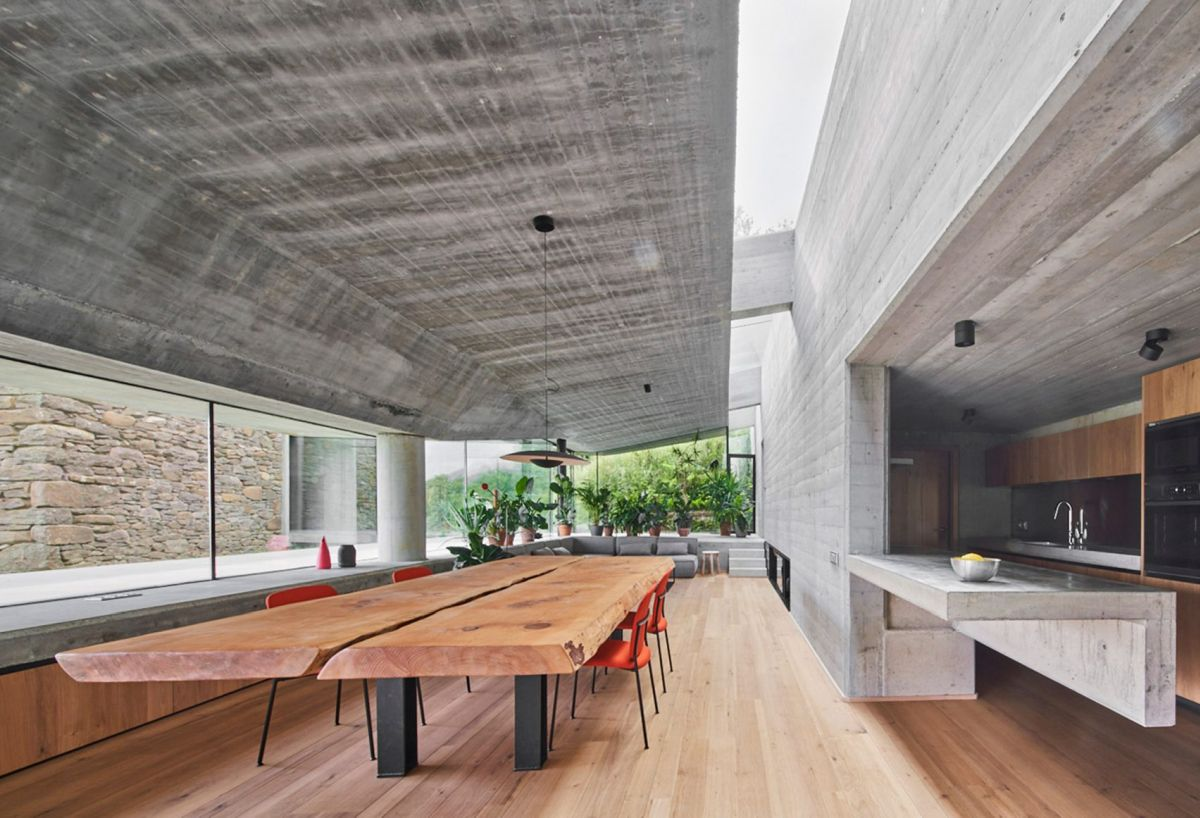 A large dining table with a solid live edge top sits parallel to the kitchen counter