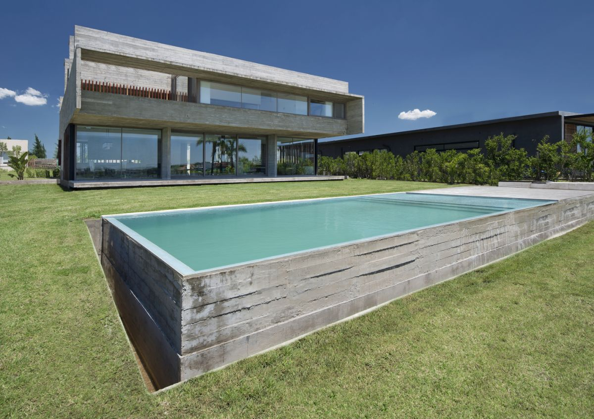 The swimming pool is rectangular and encased in concrete, just like the house