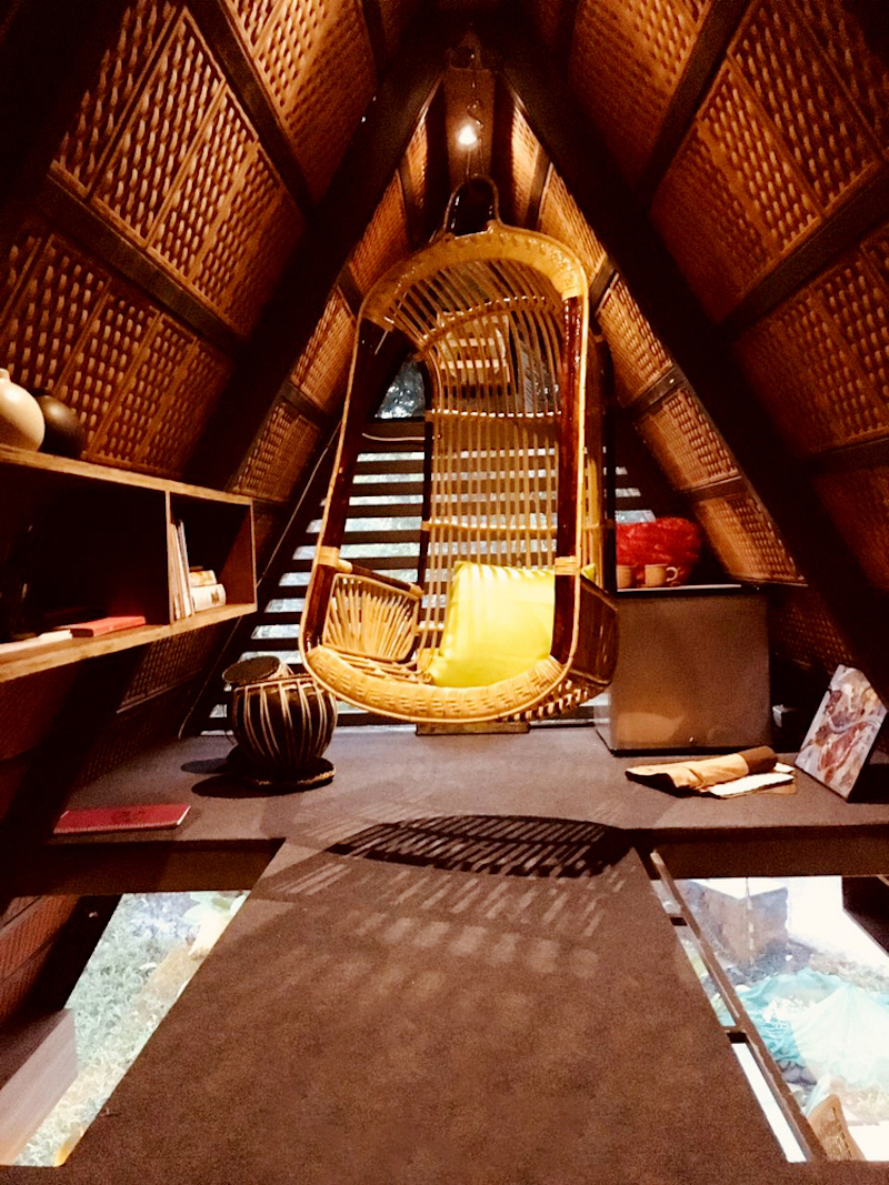 The attic serves as a leisure area and has a hanging chair and a sleeping mattress