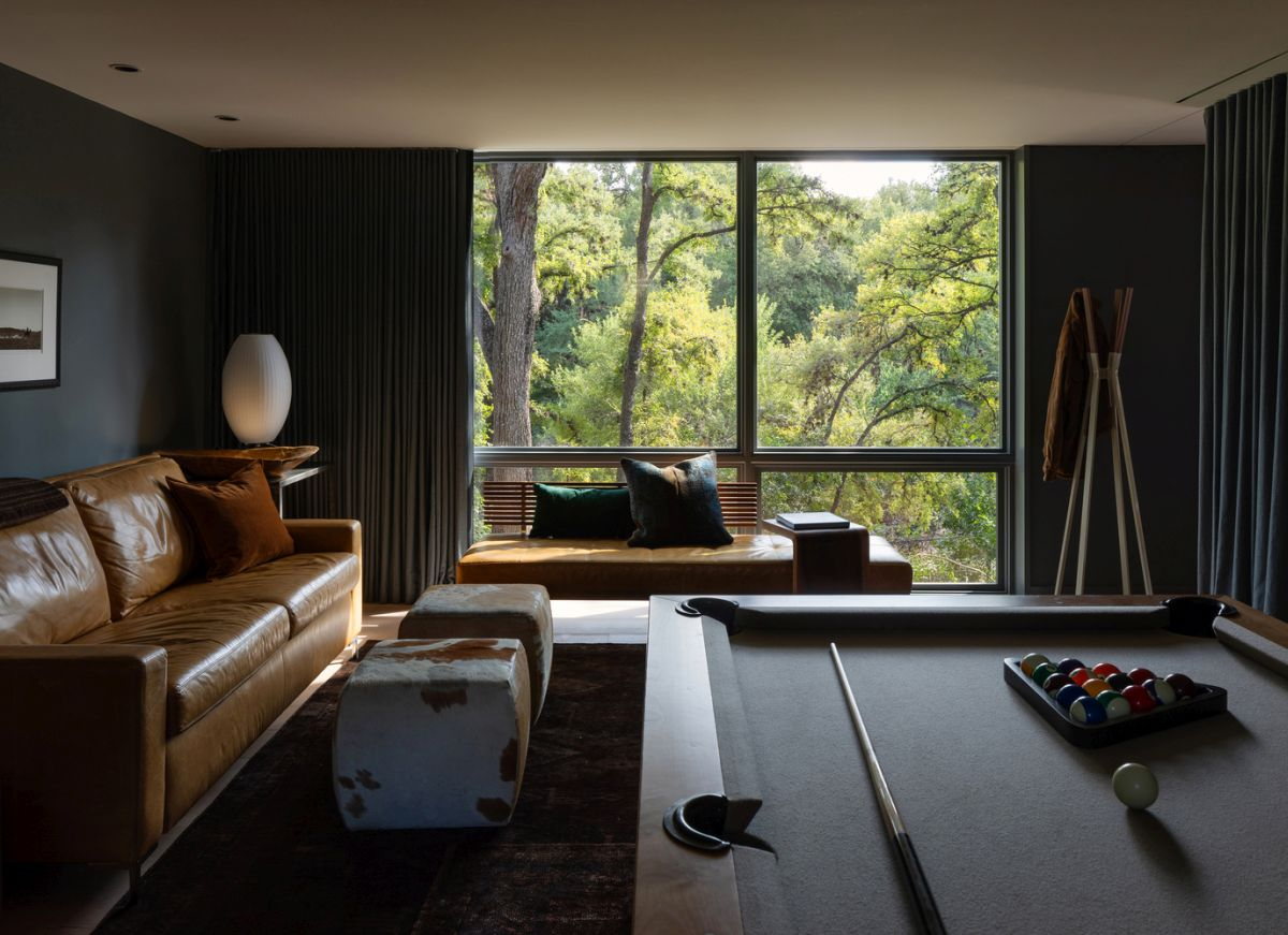 Dark colored walls give this recreational area a cozy and intimate look without fully embracing the rustic style