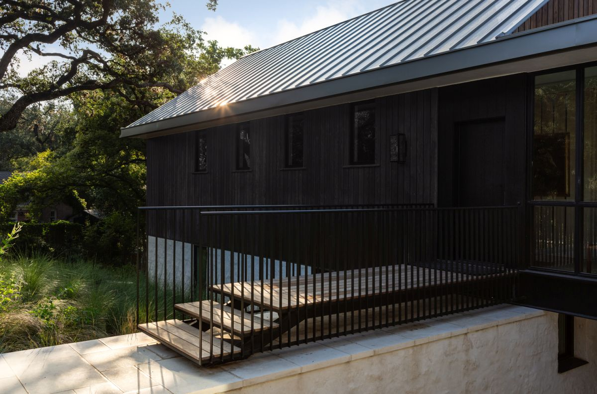 An elevated walkway leads to the main entrance which is through one of the wooden volumes