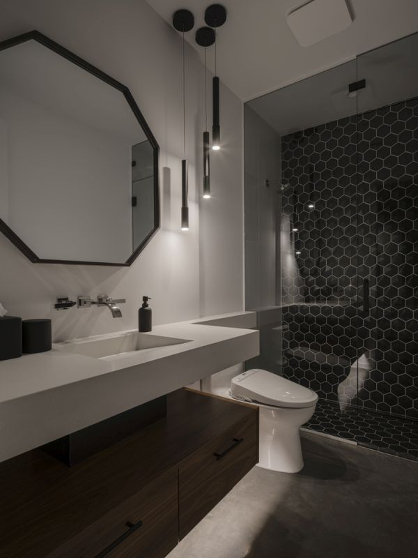 The large octagon-shaped mirror complements the honeycomb shower tiles