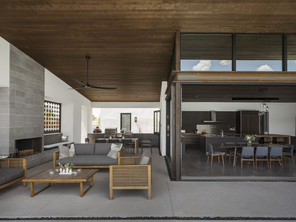 The roof extends outside creating a covered outdoor patio