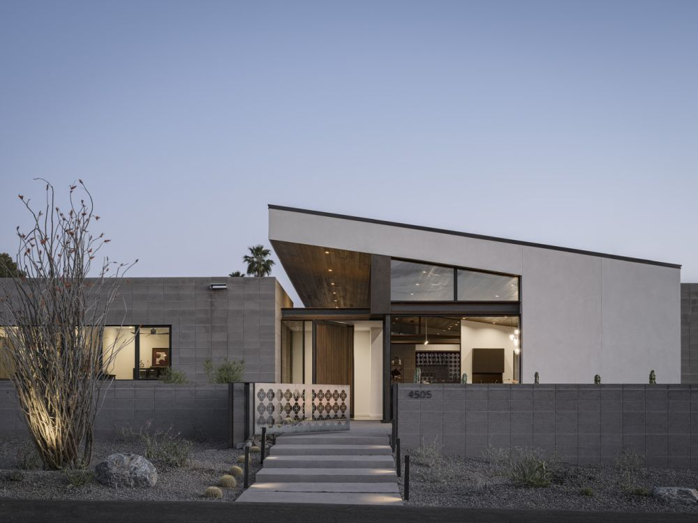 The house has prominent front entrance with an asymmetric roof extension