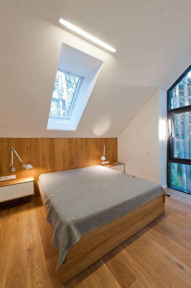 This bedroom has a small skylight centered above it and features a very simple design