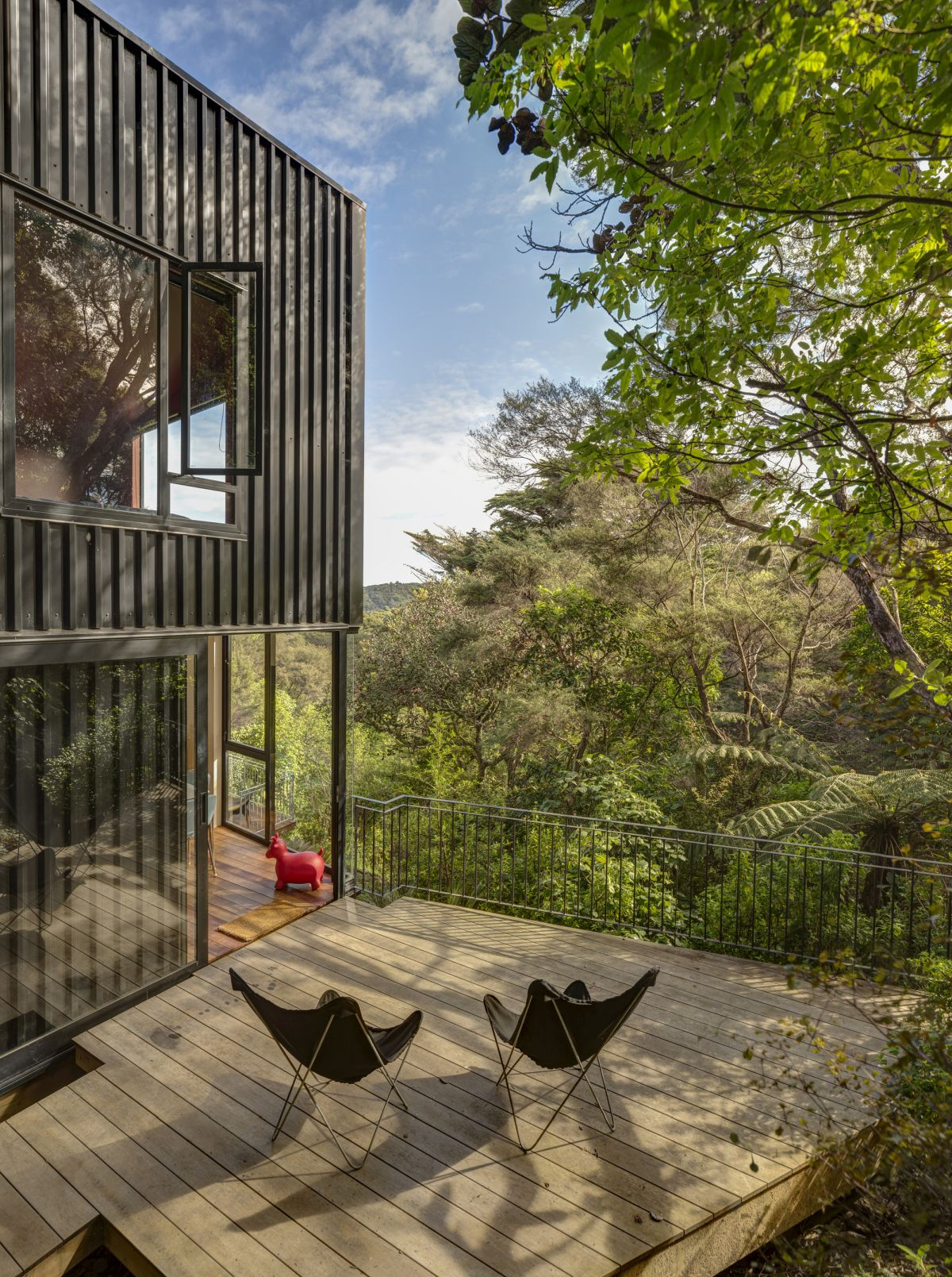 The tall and narrow structure allows the house to rise among the tall tree canopies and to make the most of its location