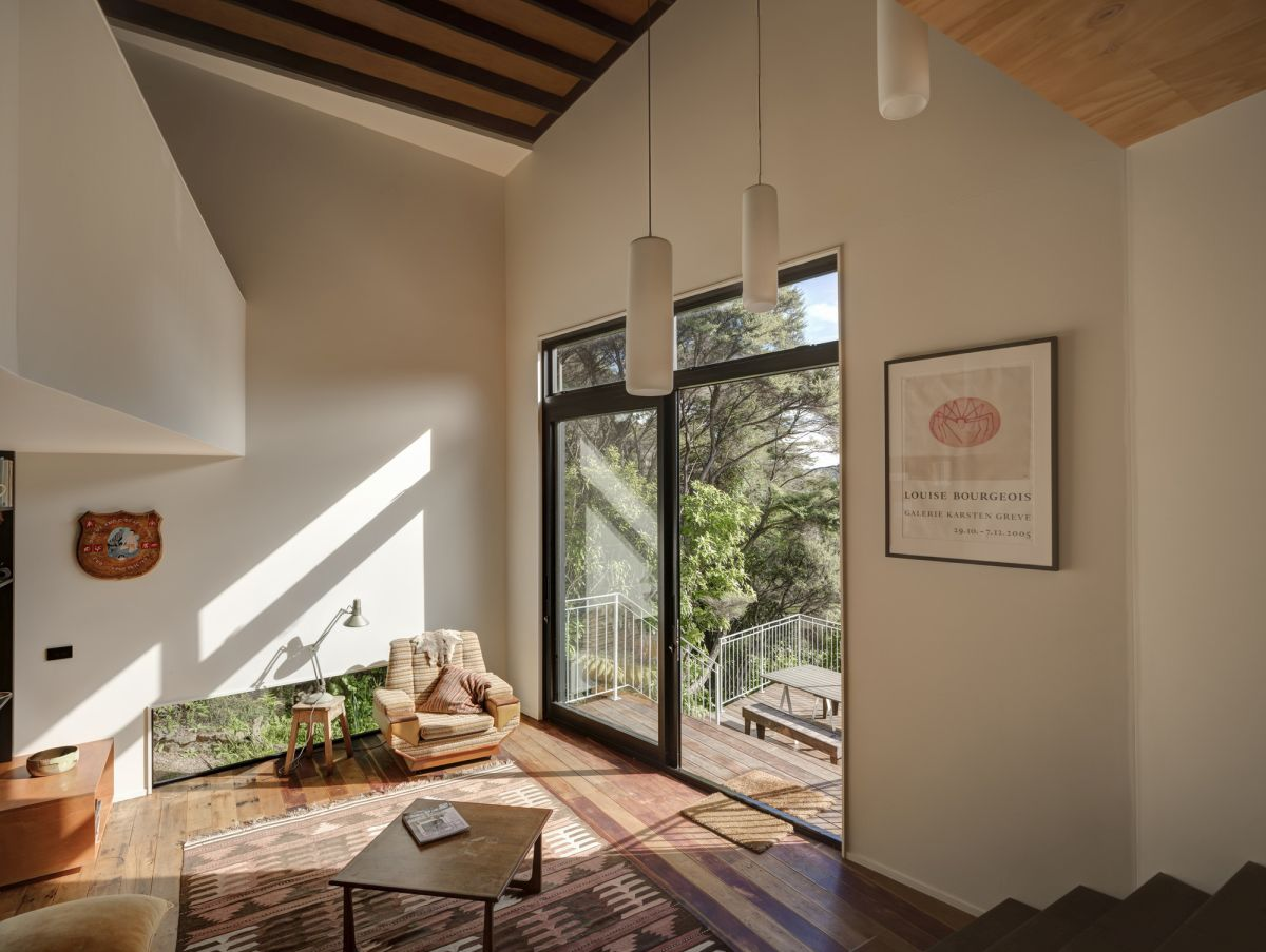 The living room has a double height ceiling and access to one of the open deck areas