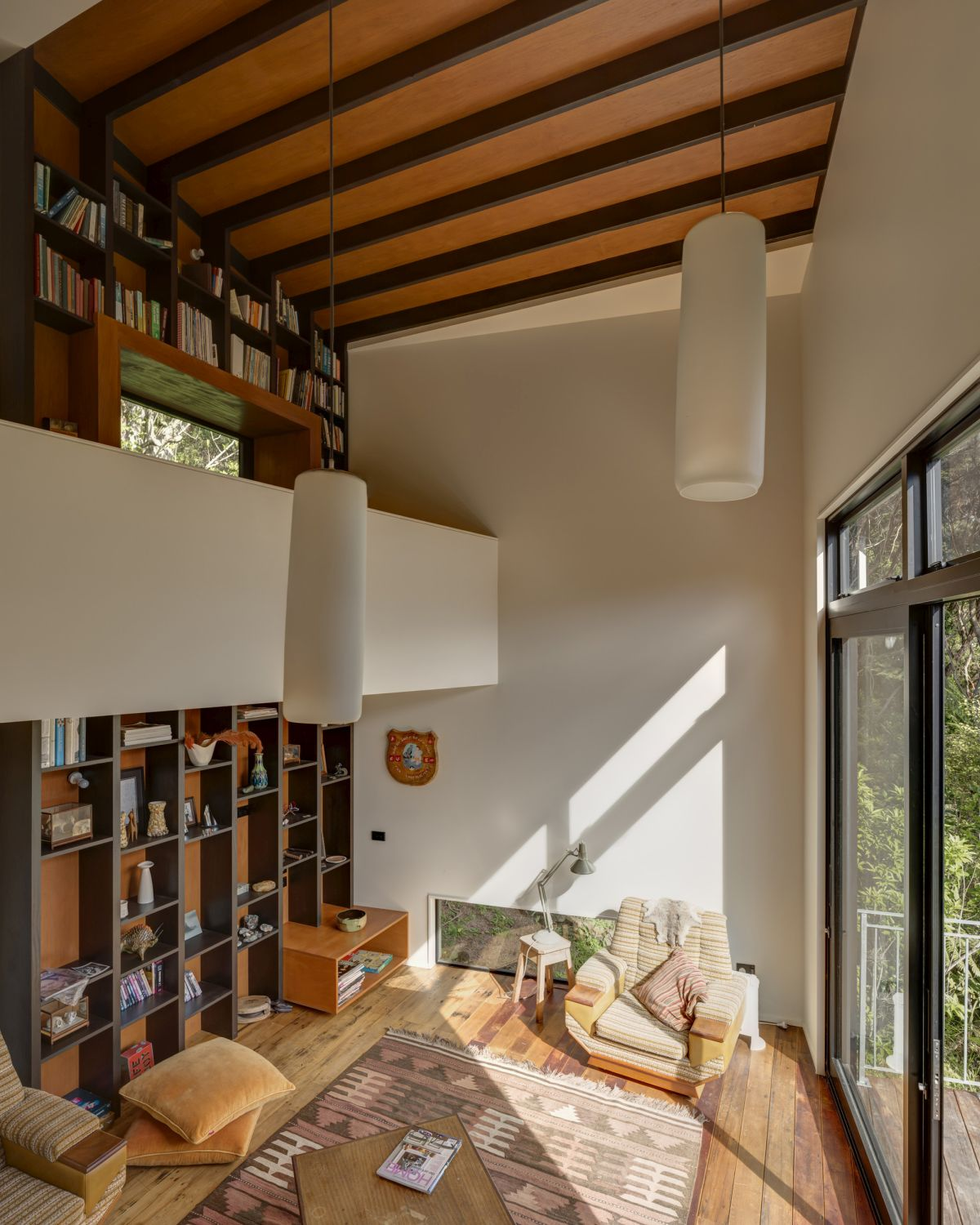 A tall wooden bookcase extends all the way up to the ceiling, emphasizing the height of the room