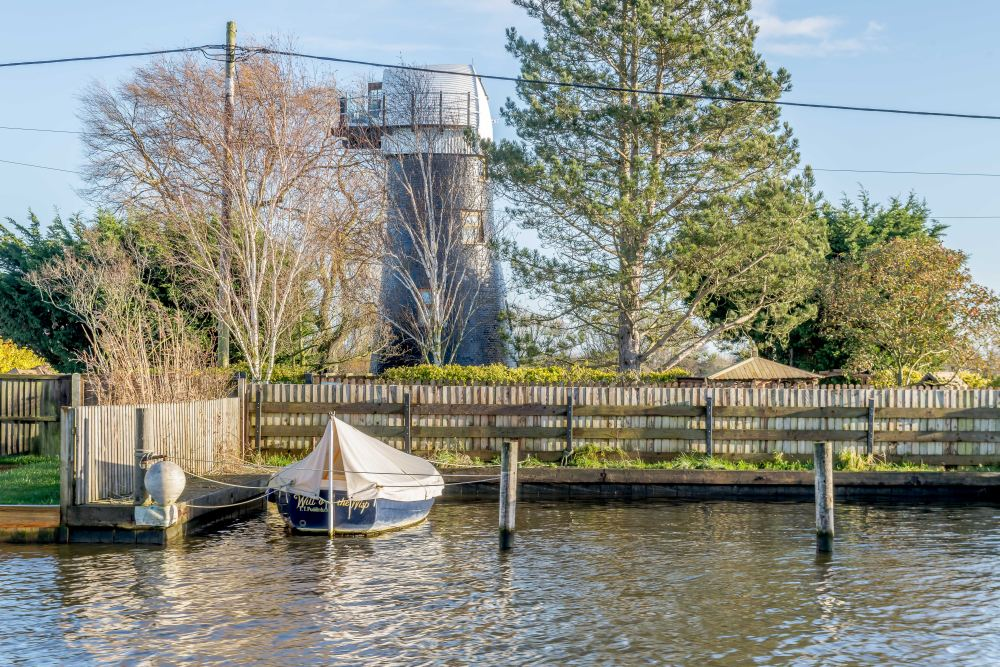 The area surrounding the windmill is beautiful with lots of greenery and water