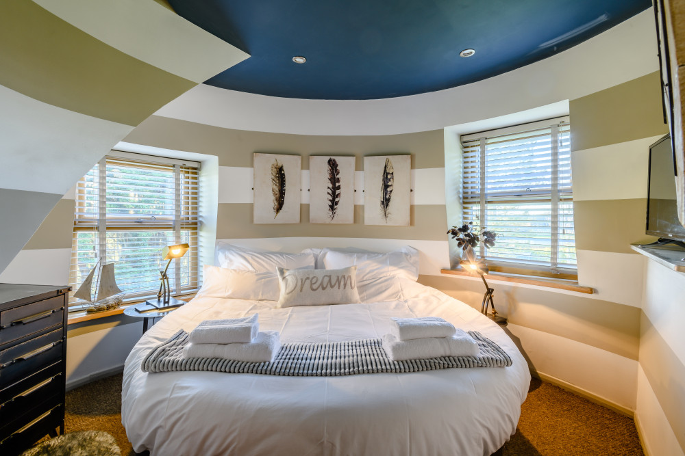 The bedroom on the second floor has a round bed and vertical stripes on the walls