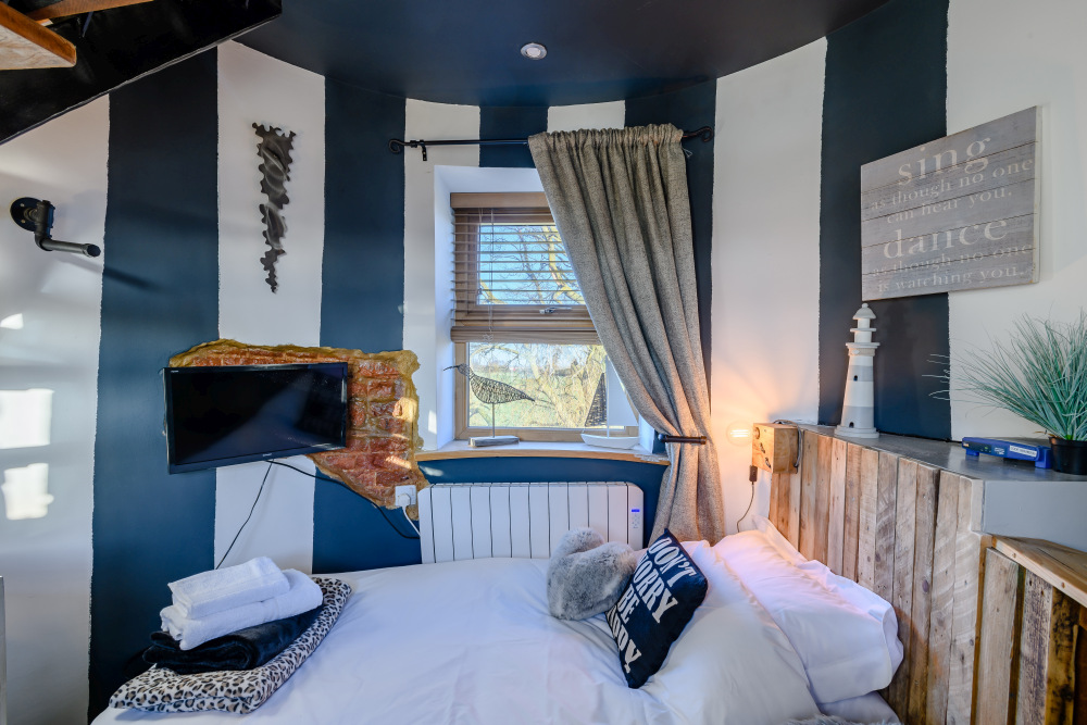 One of the bedrooms has white and dark blue striped walls and a nice nautical vibe