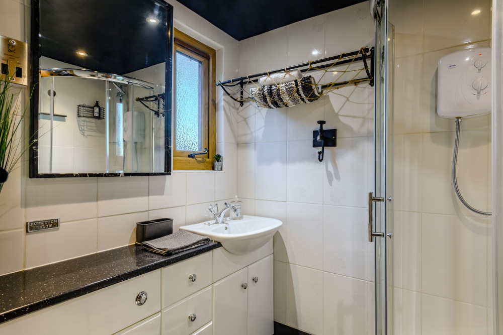 The bathroom is quite spacious and has a corner walk-in shower