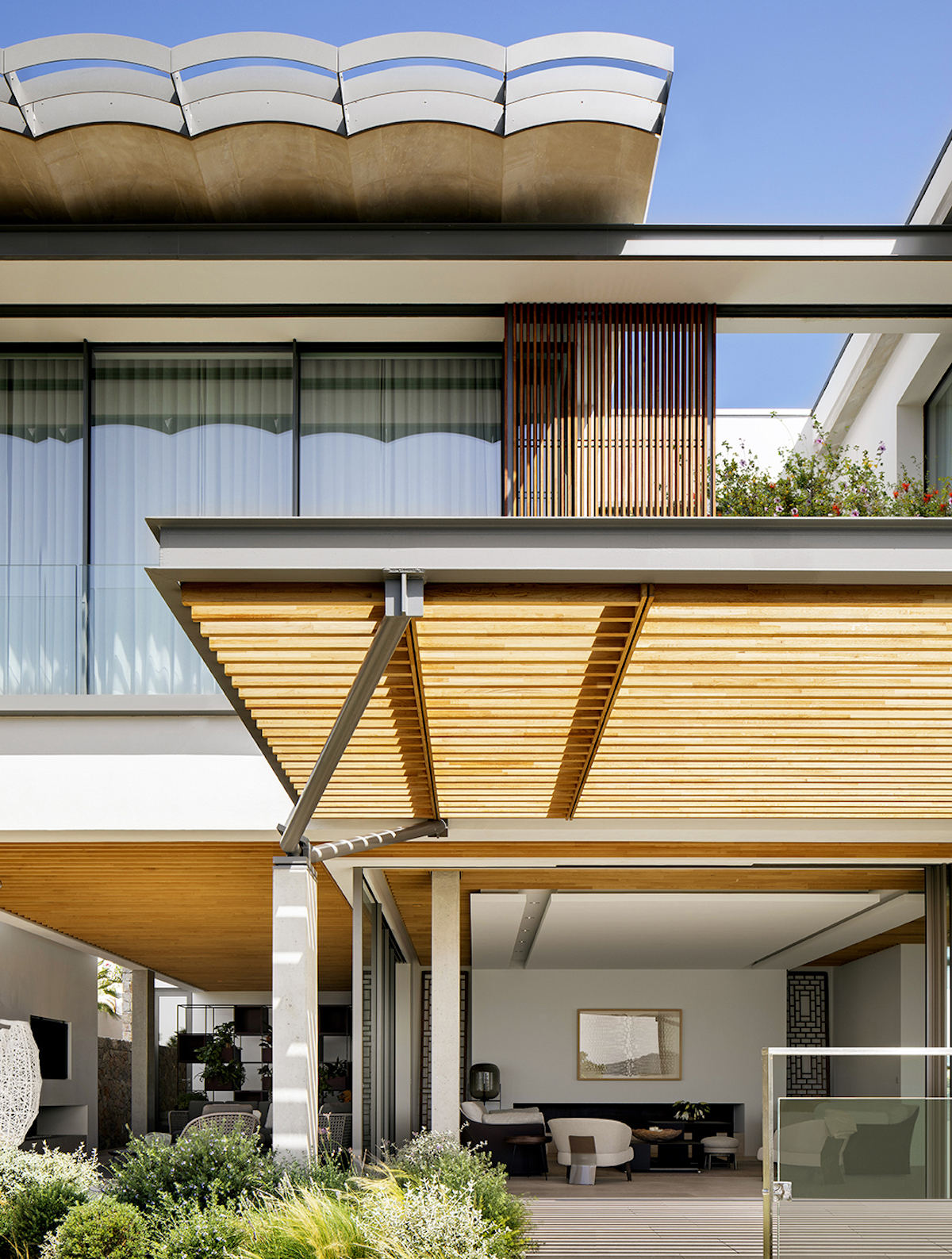 The roof has a very interesting design with traditional influences featuring a wavy form that helps the residence blend into the surroundings