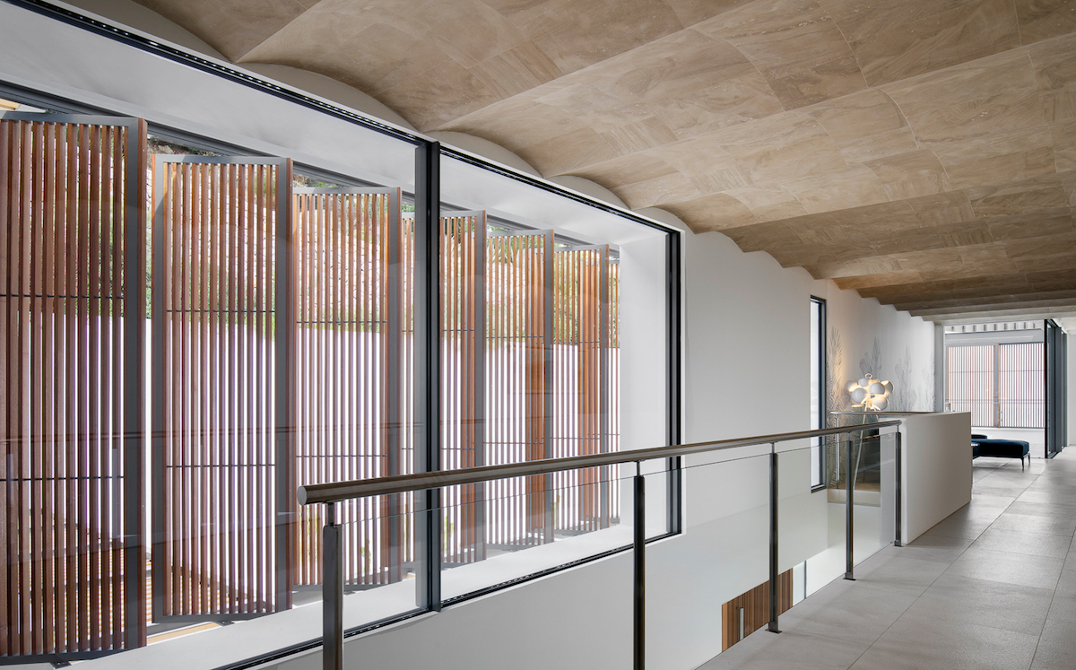 The wavy form of the roof tiles is replicated inside the residence as well, giving the spaces a particularly interesting look