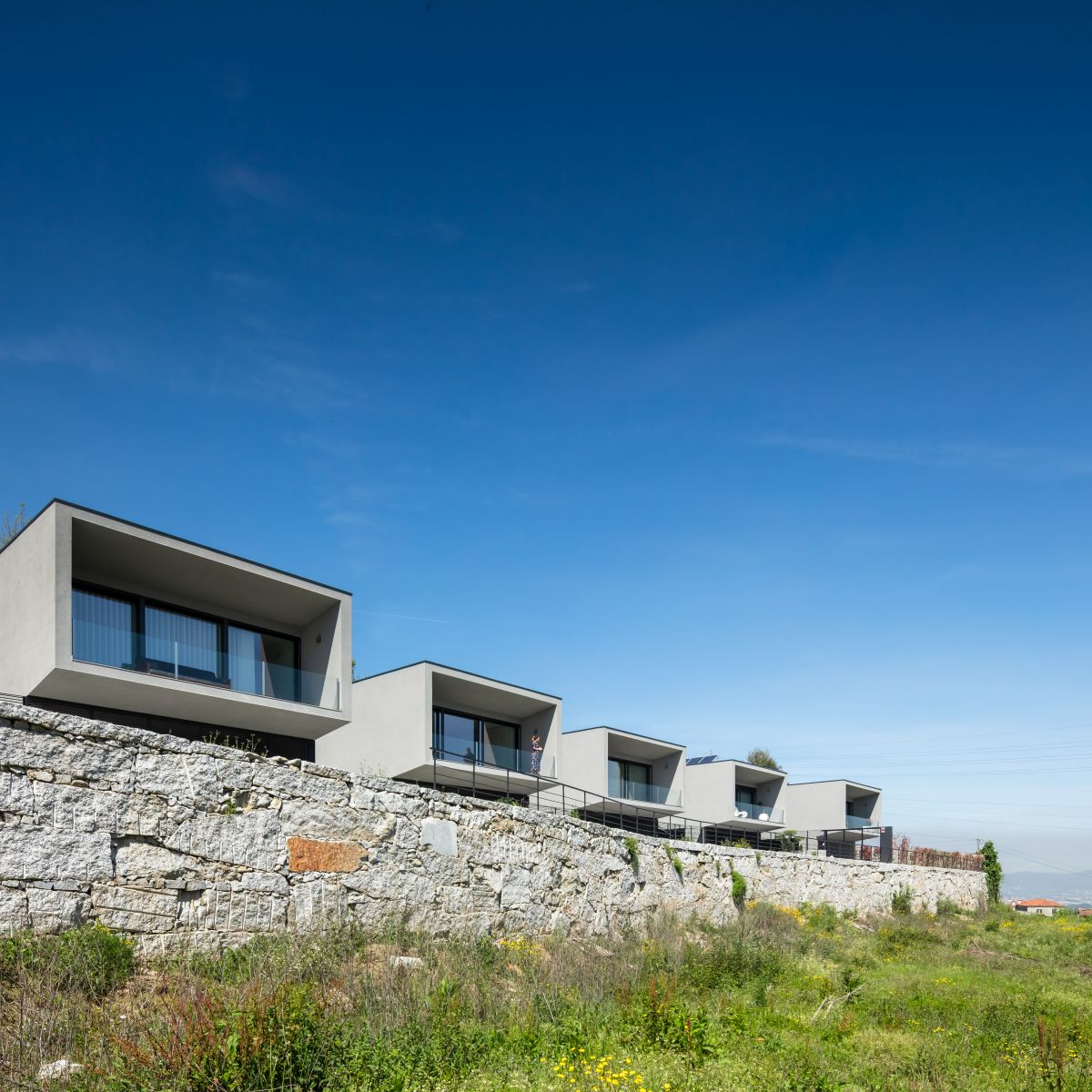 Each house has two floors, with the upper level ending in a framed terrace with glass railings