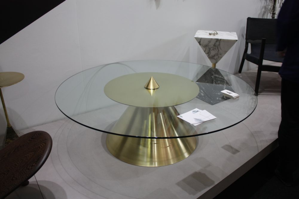 The glass top circles around the metal base and features a cute golden cone at its center