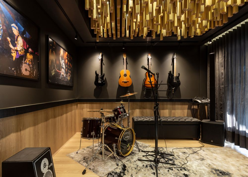 The music studio has laminate flooring which transitions onto the walls and is defined by a dark and glamorous color palette