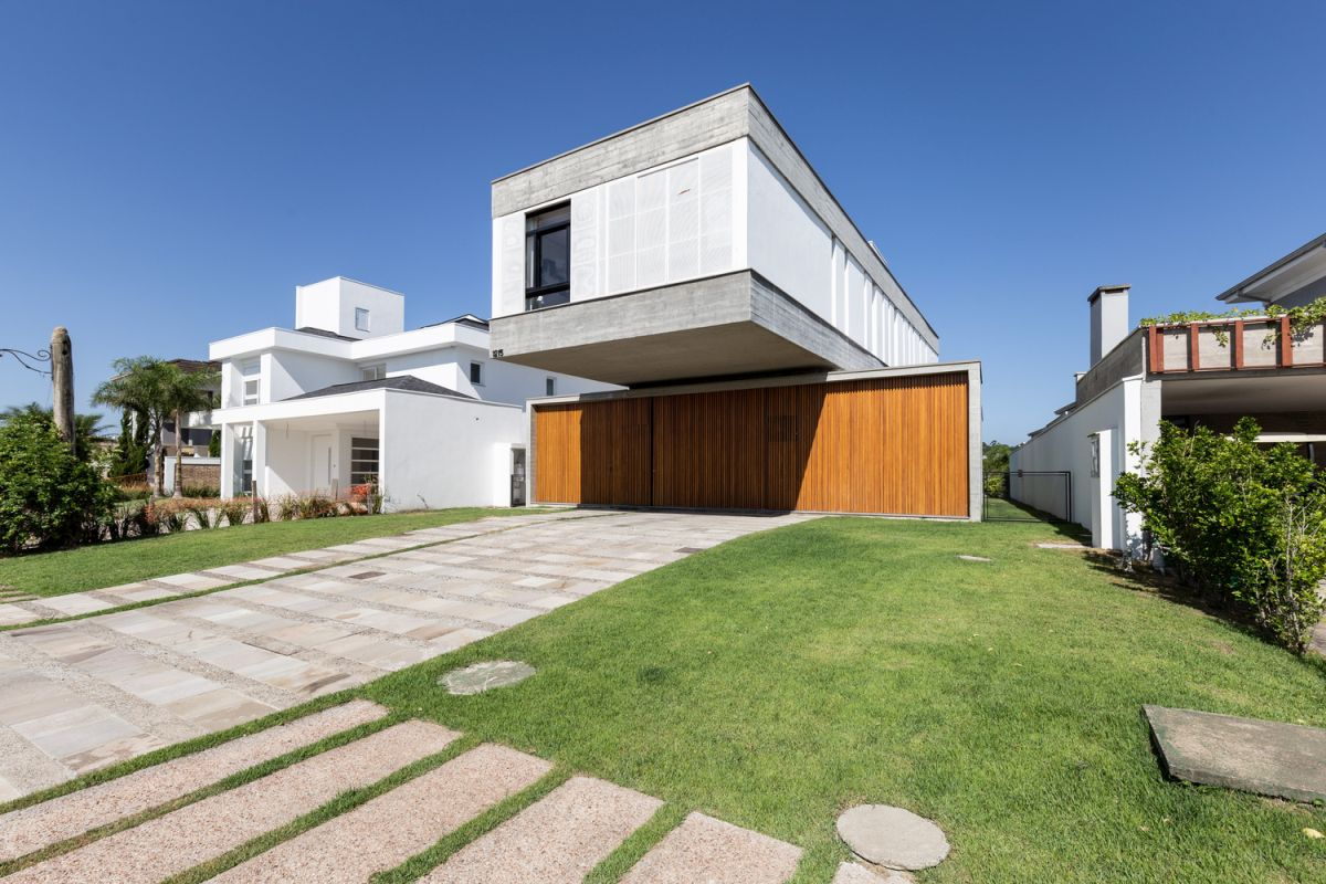 The second floor volume cantilevers over the driveway, creating a shaded area underneath