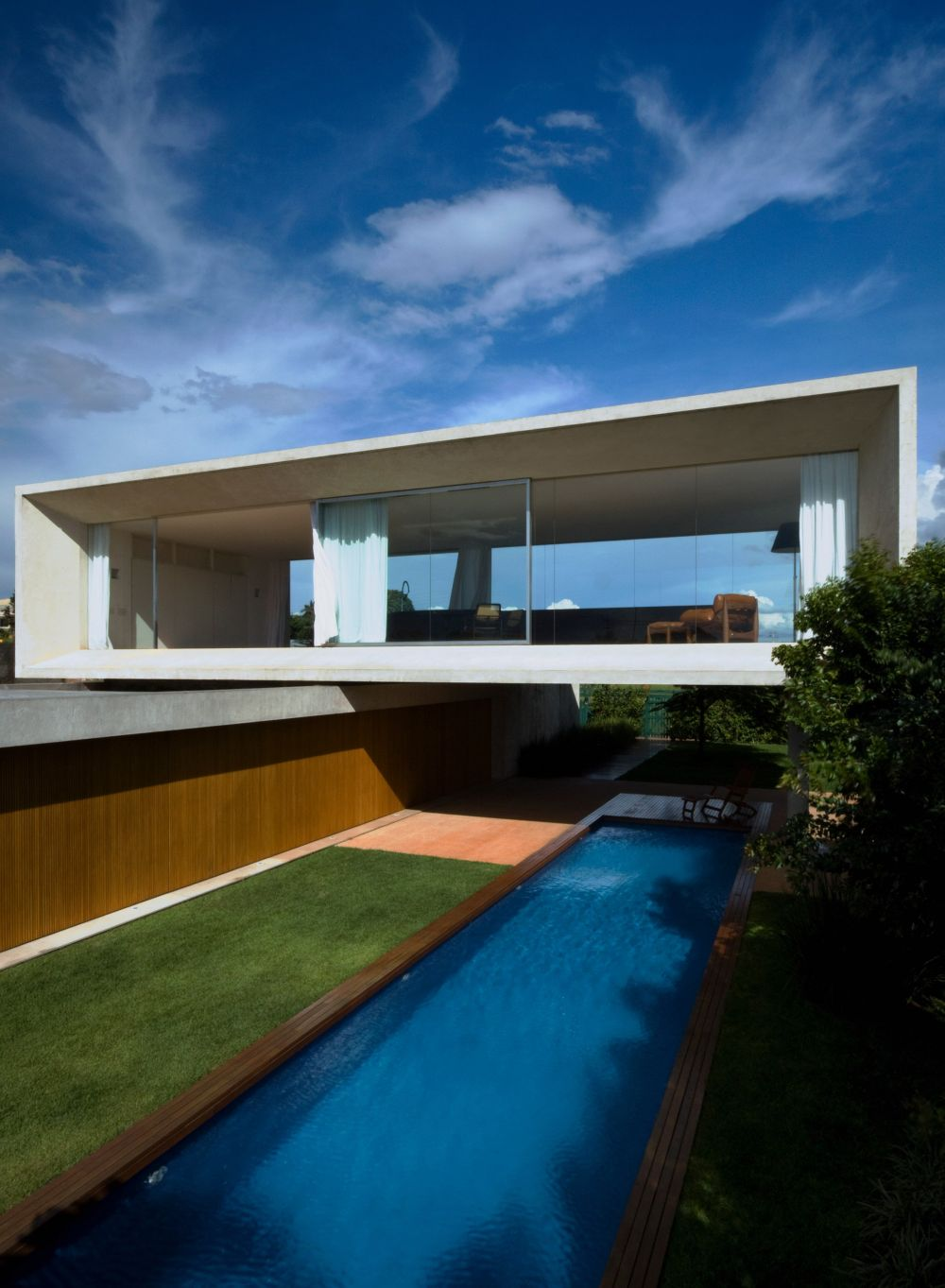 The top volume has glazed sides and hovers over a lap pool, being suspended on stilts