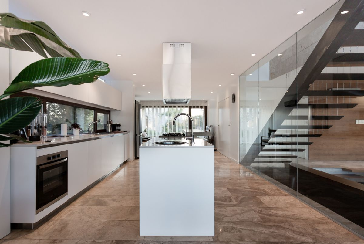 The spacious kitchen together with a cozy seating nook by the window are separated from the living room by a glass wall