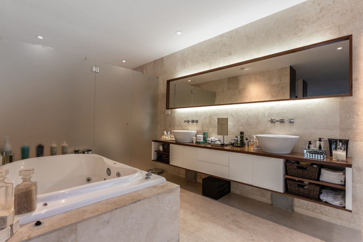 The master bathroom is large and welcoming, featuring a stylish walk-in shower with frosted glass walls