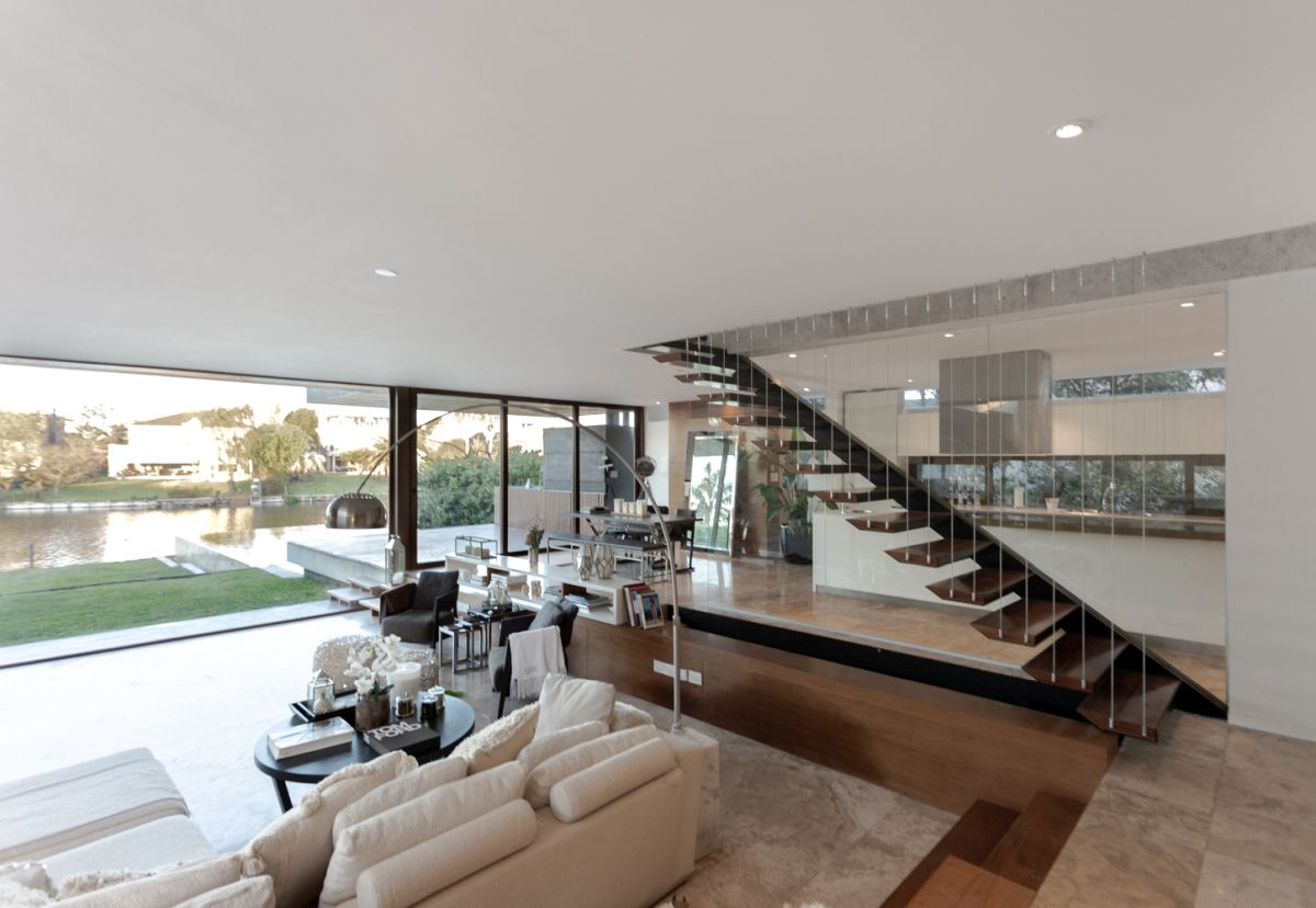 The metal staircase which connects the two floors is positioned between the living room and the kitchen