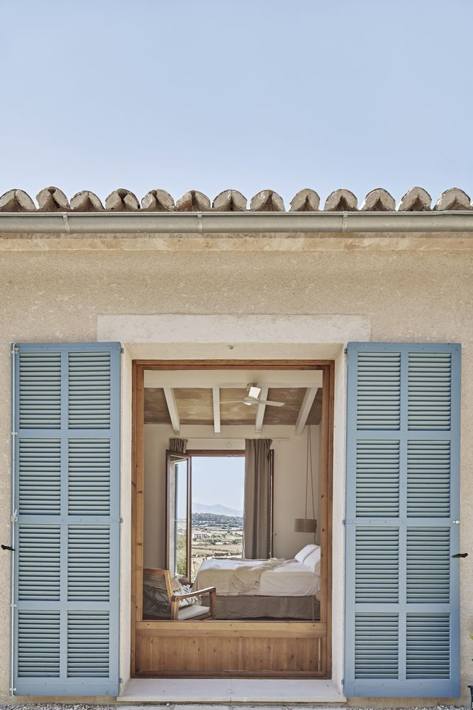 The large bedroom windows have wooden shutters with a retro blue finish
