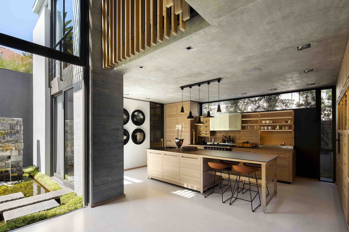 The kitchen is open and part of a large social plan with sliding glass doors that lead into the garden