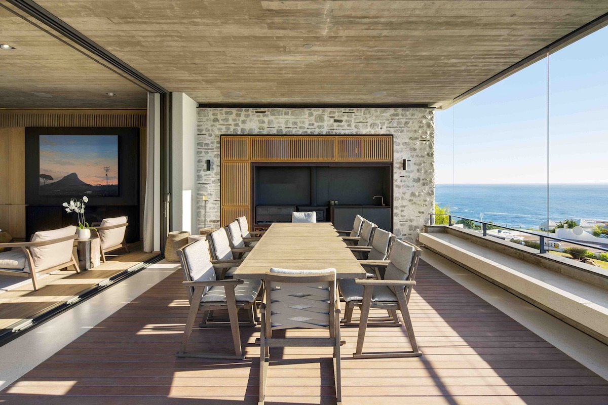 The dining area has a glazed facade that invites a panoramic view of the sea inside the house