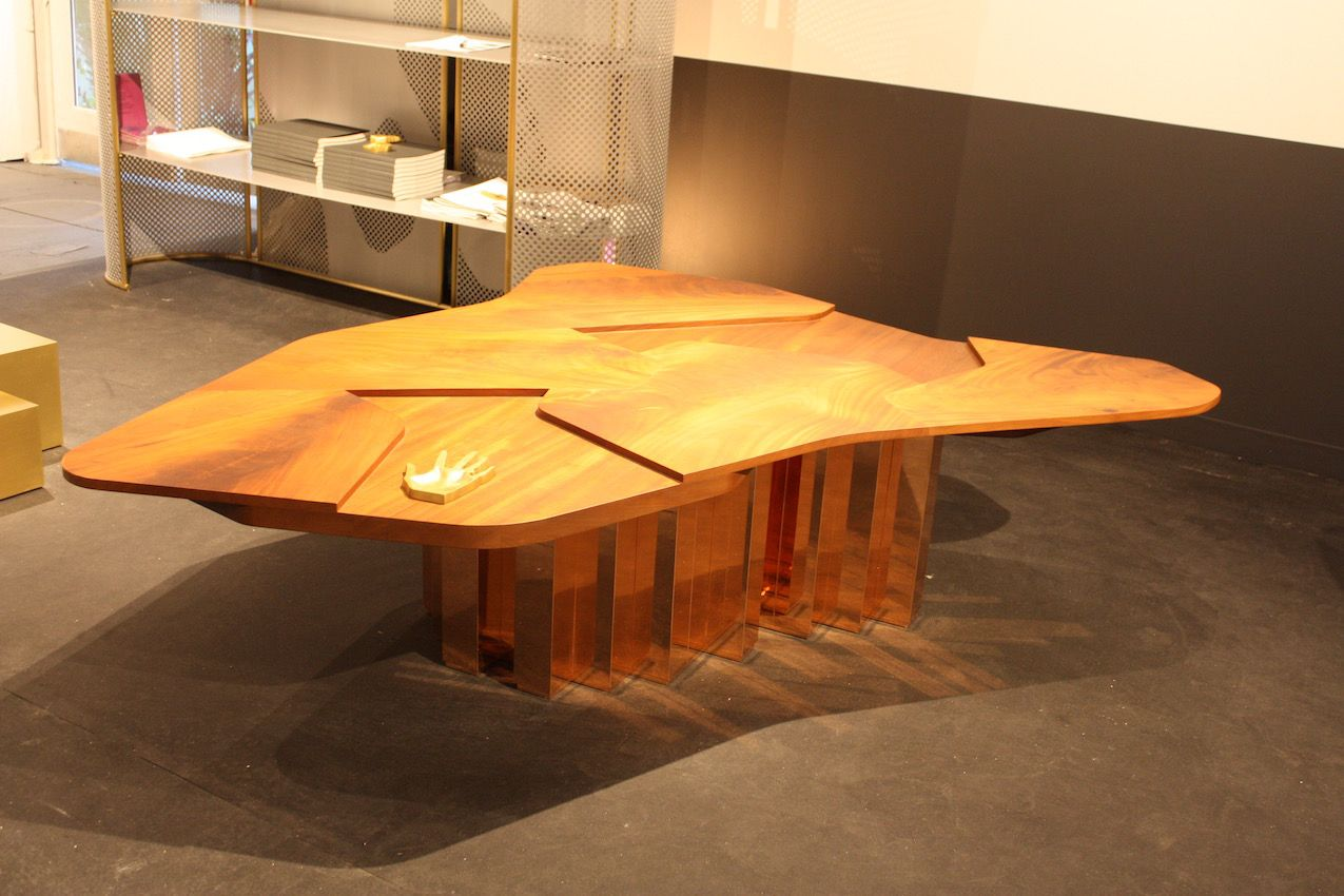 Gorgeous mahogany wood grain is enhanced by the uneven surface of this coffee table designed by Karen Chekerdjian. The shiny copper plated brass base provides a modern counterpoint to the warm wood. From the Carwan Gallery.