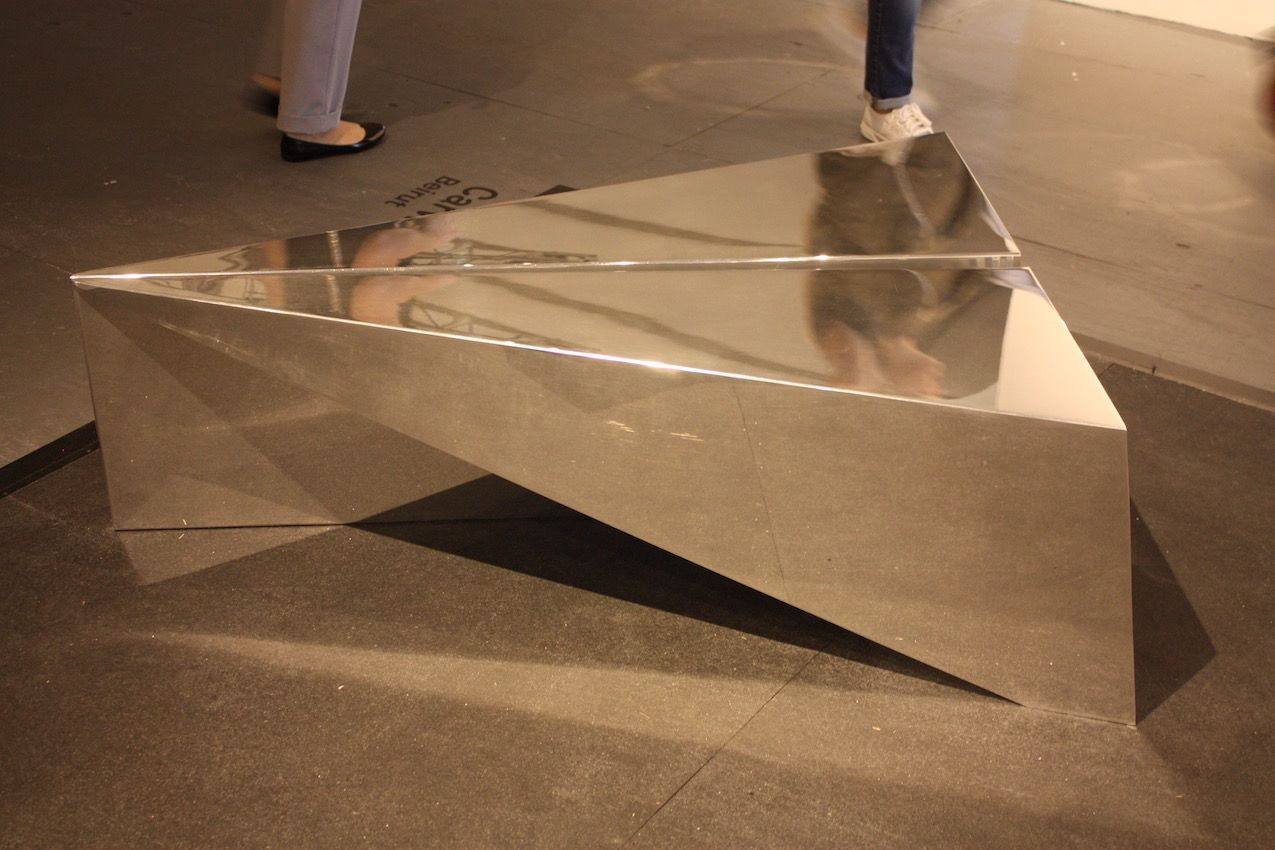 """Chekerdjian's IQAR table """"blurs the line between origami and metallurgy,"""" says the description. It is made from one sheet of aluminum, and folded by hand."""