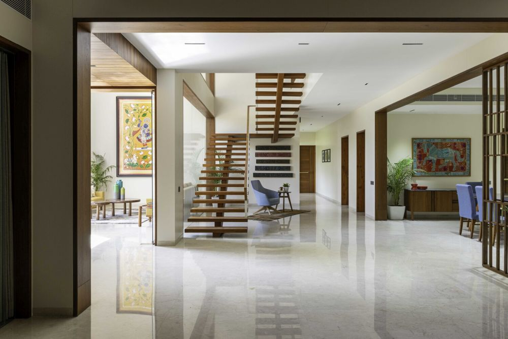 A floating wood staircase connects the social areas to the private upper floor