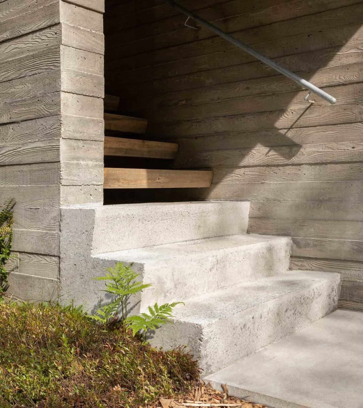 The entrance is marked by a set of concrete stairs which then transition into a wooden staircase