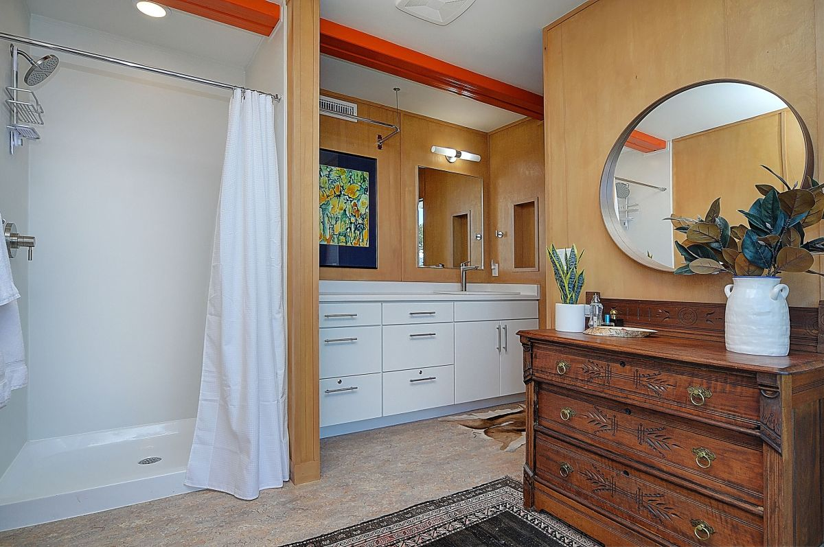 The bathrooms are designed in the same warm, mid-century modern style as the rest of the house