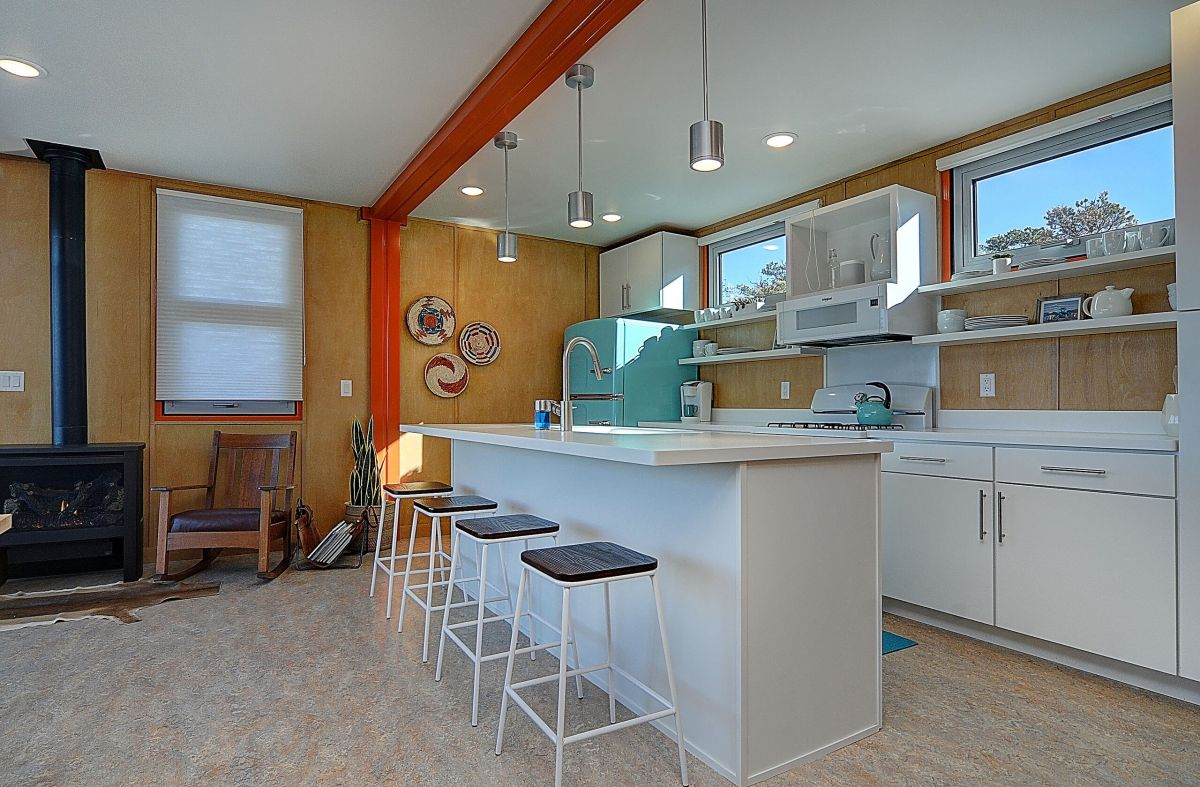The kitchen featured white cabinetry and matching countertops, with a beautiful retro fridge in the corner