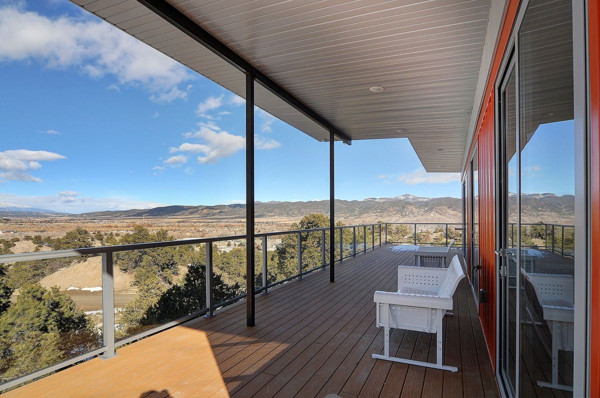 The large deck is sheltered beneath the overhanging roof and takes full advantage of the beautiful scenery