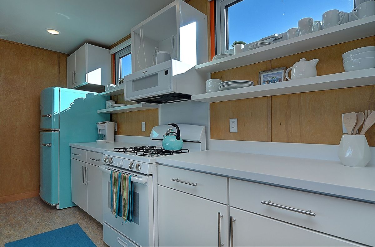 The windows in the kitchen are placed up high above the backsplash and the wall-mounted shelves