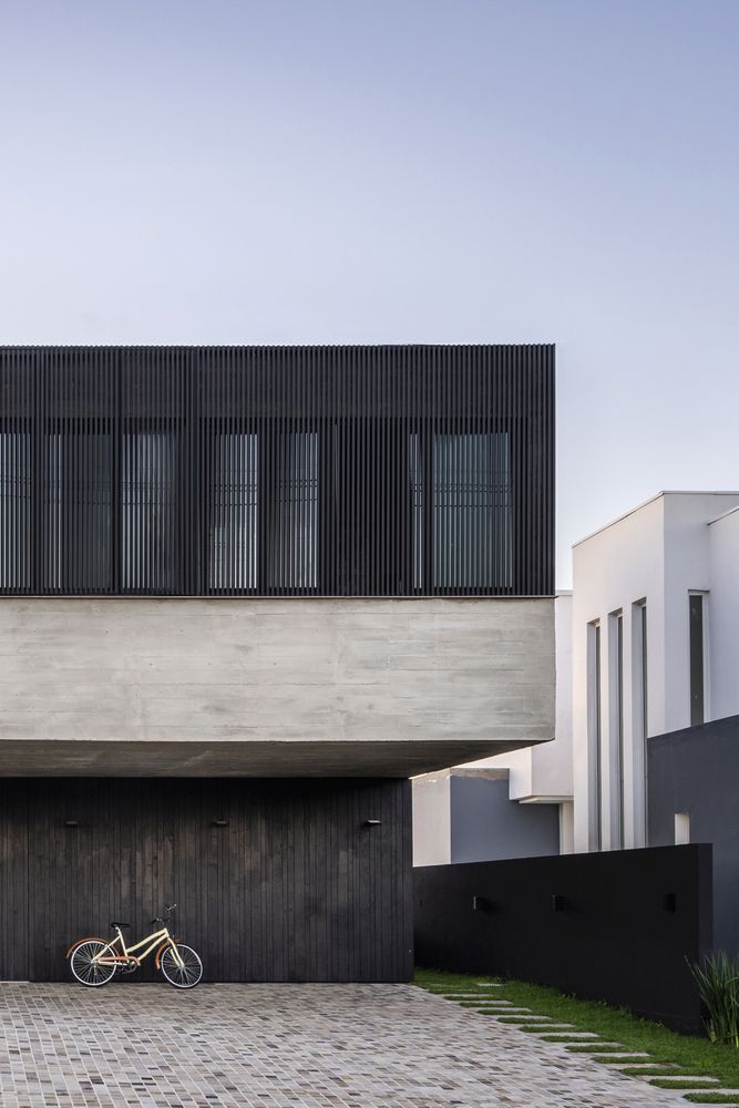 The black wood and the louvers add a sophisticated look to the house and go really well with the concrete