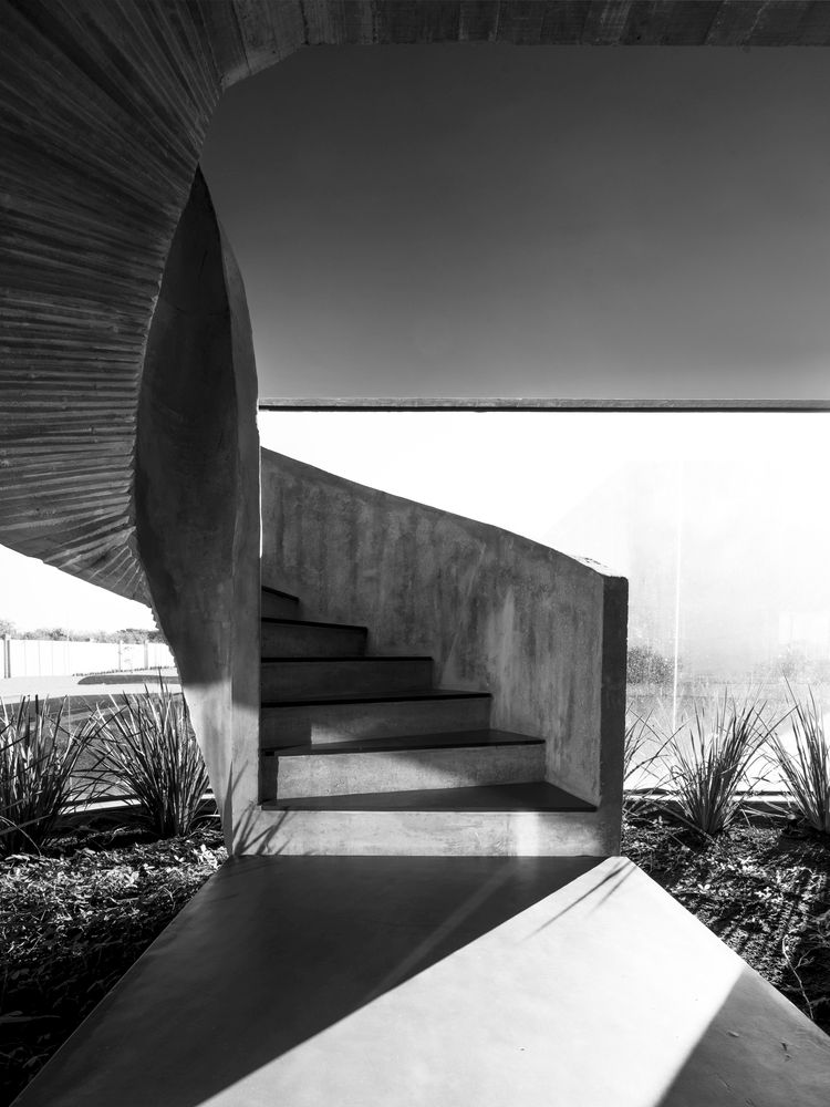 The concrete staircase has a graceful twisting design and is the main focal point of the entire building