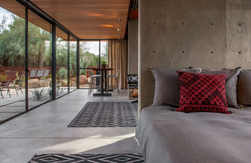 The polished concrete flooring maintains a neutral look throughout, giving the guest house a modern-industrial feel