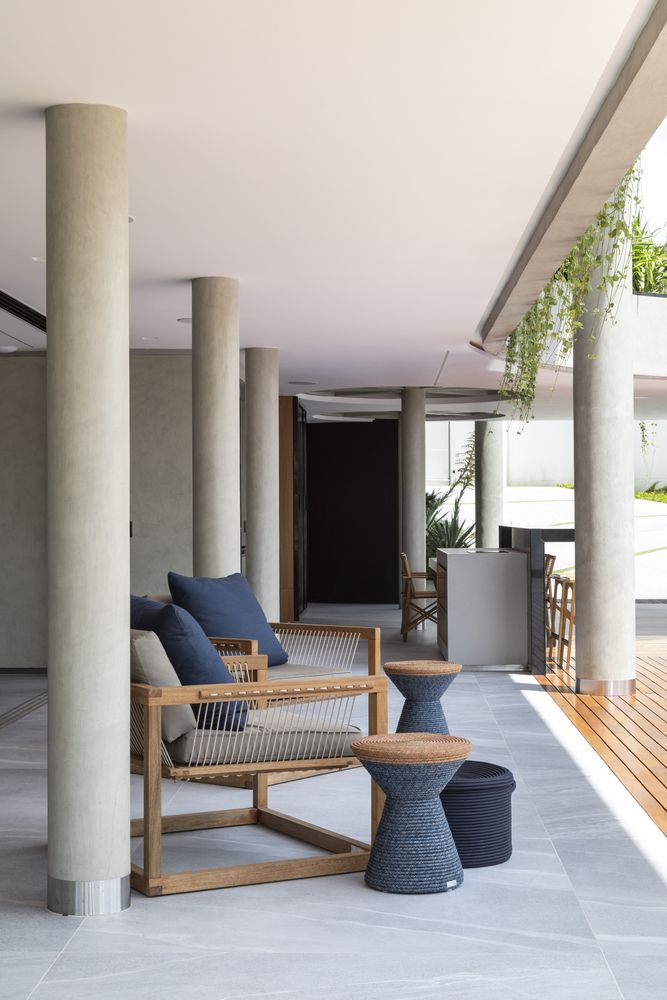 A series of round structural columns are spread throughout the ground floor and extend outside
