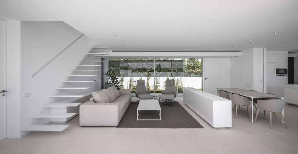 Inside, the kitchen, living room and dining area share the same volume with a sleek staircase serving as a backdrop