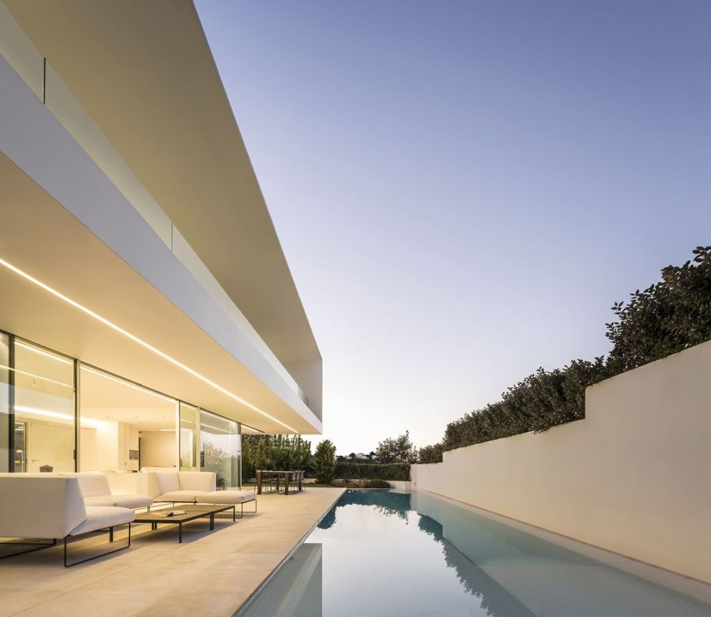 The cantilevered upper level forms a protective roof over the poolside deck, making the indoor-outdoor transition even smoother