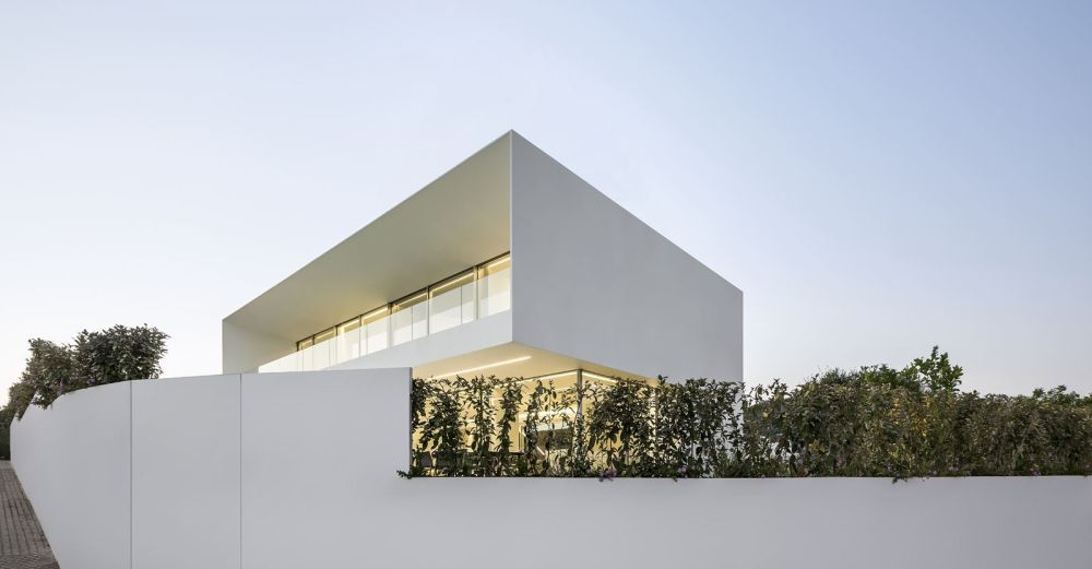 A crisp white curved wall frames the site offering it privacy from the street without blocking the views, thanks to the uneven topography